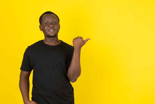 Portret młodego mężczyzny stojącego i wskazującego kciukiem na żółtą ścianę