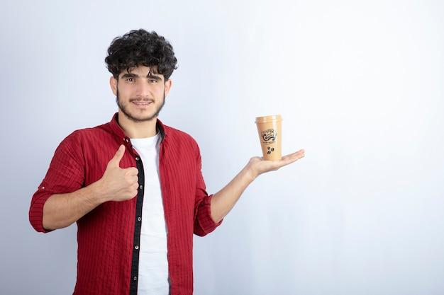 Portret młodego mężczyzny stojącego na białym tle z filiżanką kawy. wysokiej jakości zdjęcie