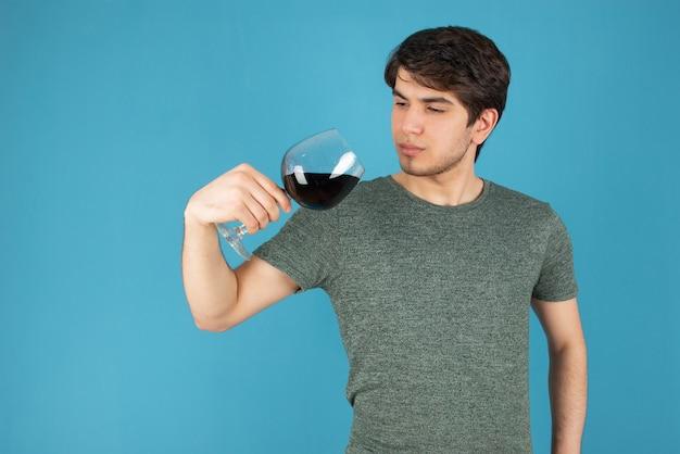 Portret młodego mężczyzny stojącego przy lampce wina na niebiesko.