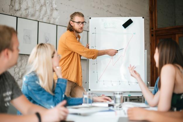 Portret młodego mężczyzny stojącego w pobliżu płyty i rozmawiającego z kolegami w biurze
