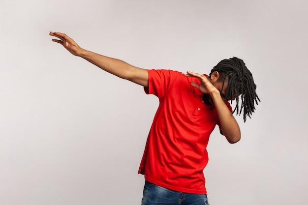 Portret młodego mężczyzny stojącego w pozie tanecznej dab, mem internetowy, świętuje sukces.