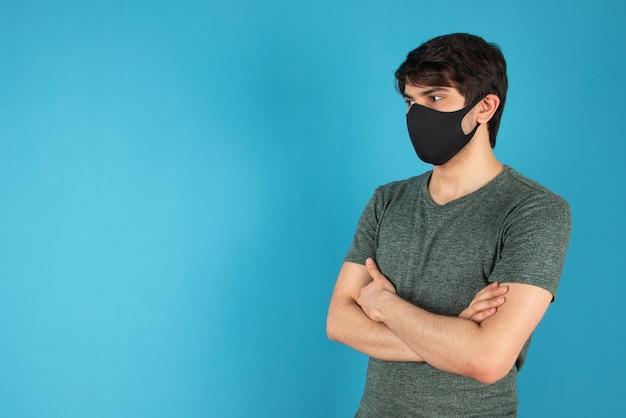 Portret młodego mężczyzny stojącego z czarną maską medyczną na niebiesko.