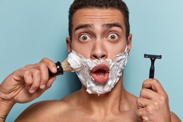 Portret młodego mężczyzny stosowania kremu do golenia