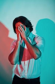 Portret młodego mężczyzny stylowe, który stoi w neony w studio.