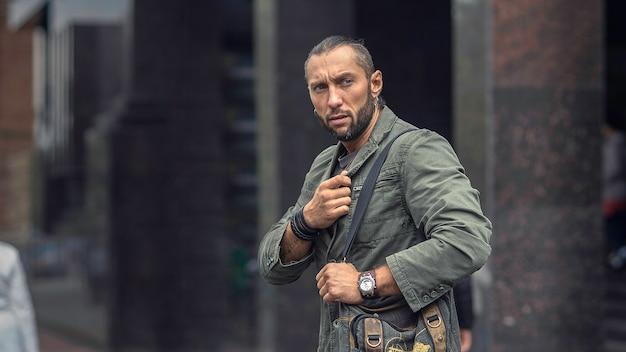 Portret młodego mężczyzny stylowy z torbą na ulicy sity europejskiej.