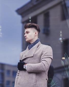 Portret młodego mężczyzny sukcesu w eleganckim płaszczu w mieście