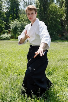 Portret młodego mężczyzny taekwondo ćwiczeń w parku przyrody
