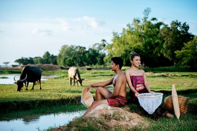 Portret młodego mężczyzny topless siedzący w pobliżu ładnej kobiety w pięknych ubraniach w wiejskim stylu życia