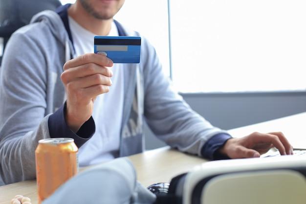 Portret młodego mężczyzny trzyma i za pomocą karty kredytowej do doładowania pieniędzy w grze.