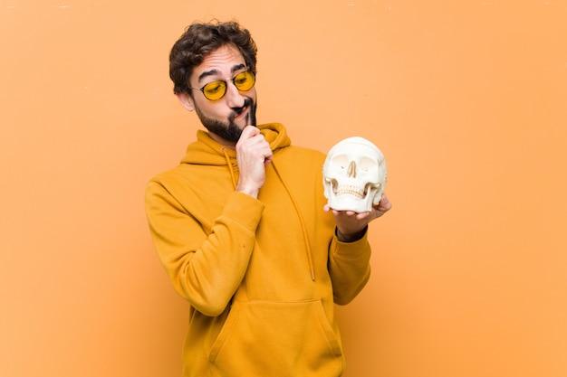 Portret młodego mężczyzny trzyma ludzką czaszkę