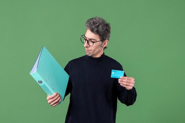 Portret młodego mężczyzny trzymającego dokument i kartę kredytową na zielonym tle natura bank nauczyciele męskie pieniądze