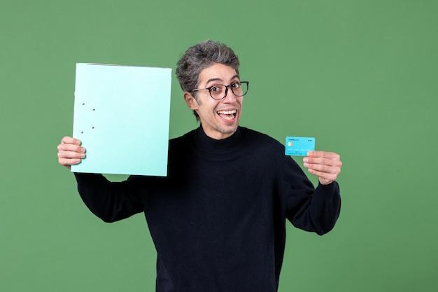 Portret młodego mężczyzny trzymającego dokument i kartę kredytową na zielonym tle natura banku nauczyciele pieniędzy męskich