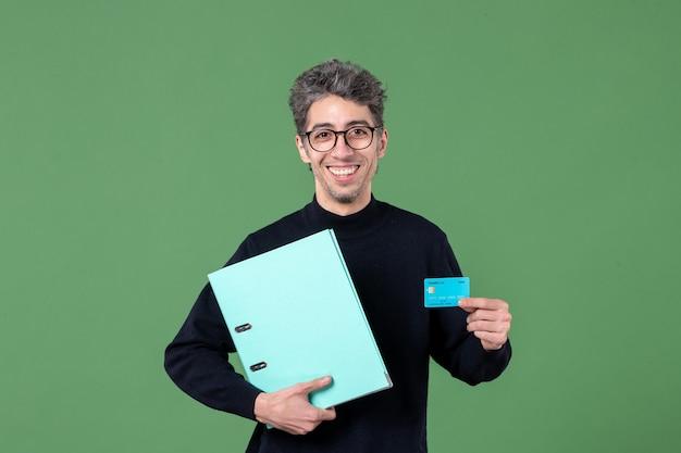 Portret młodego mężczyzny trzymającego dokument i kartę kredytową na zielonym tle nauczyciel pieniądze w banku męska praca