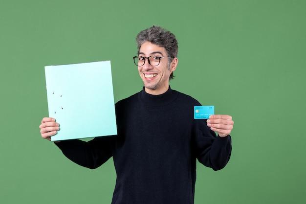 Portret młodego mężczyzny trzymającego dokument i kartę kredytową na zielonym tle nauczyciel pieniędzy z banku męskiego