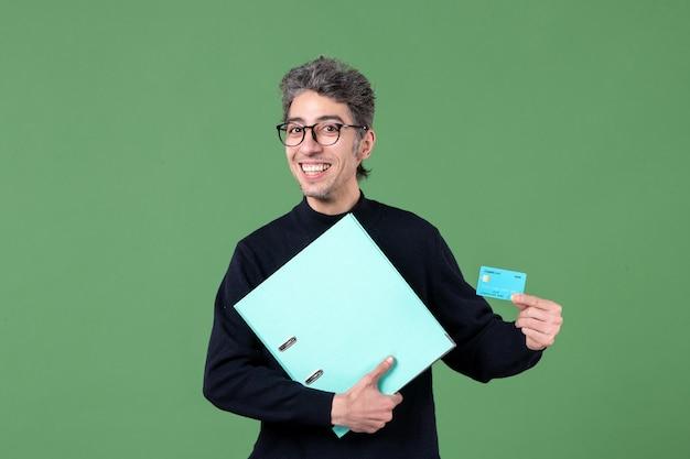 Portret młodego mężczyzny trzymającego dokument i kartę kredytową na zielonym tle nauczyciele natura pieniądze mężczyzna praca bank