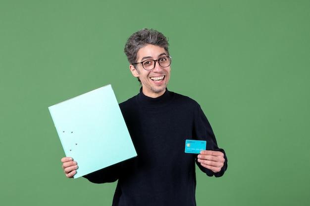 Portret młodego mężczyzny trzymającego dokument i kartę kredytową zielone tło nauczyciel banku natura pieniądze mężczyzna zdjęcie