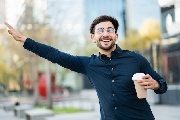 Portret młodego mężczyzny trzymającego filiżankę kawy i podnosząc rękę, aby wezwać taksówkę na zewnątrz na ulicy