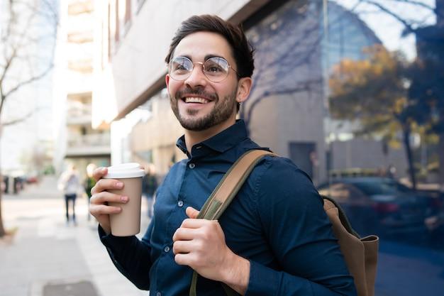 Portret młodego mężczyzny trzymającego filiżankę kawy podczas spaceru na ulicy na ulicy. koncepcja miejska i styl życia.