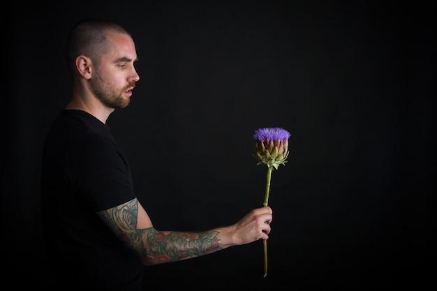 Portret młodego mężczyzny trzymającego fioletowy kwiat karczocha na czarno