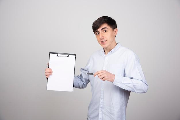 Portret młodego mężczyzny trzymającego pusty schowek na szarej ścianie.