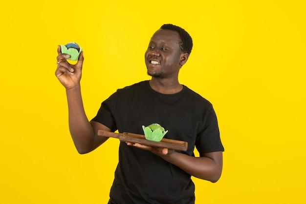 Portret młodego mężczyzny trzymającego pyszne babeczki przed żółtą ścianą
