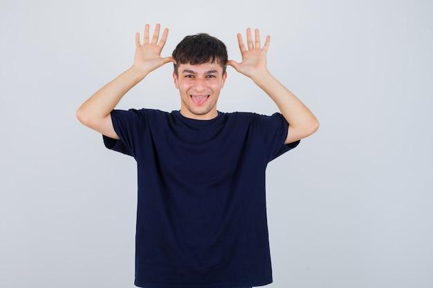 Portret młodego mężczyzny trzymającego się za ręce w pobliżu głowy jak uszy, wystający język w czarnej koszulce i patrząc rozbawiony widok z przodu