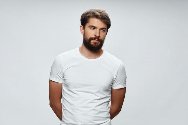 Portret młodego mężczyzny w białej koszulce na białej powierzchni