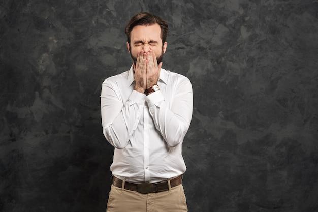 Portret młodego mężczyzny w białej koszuli kichanie