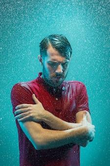 Portret młodego mężczyzny w deszczu