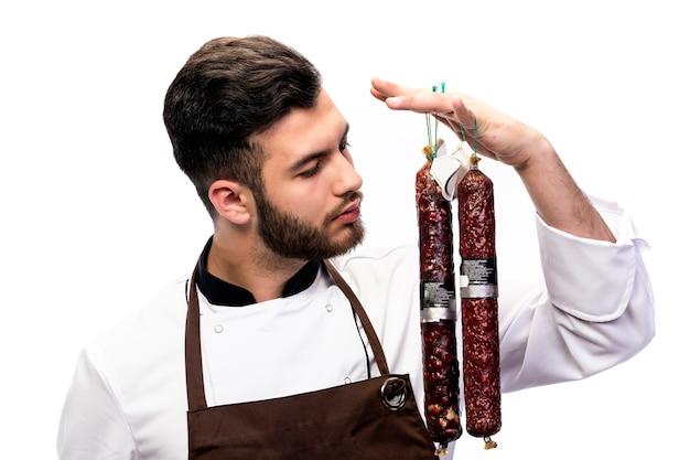 Portret młodego mężczyzny w fartuch szefa kuchni. kucharz wącha salami na białym tle