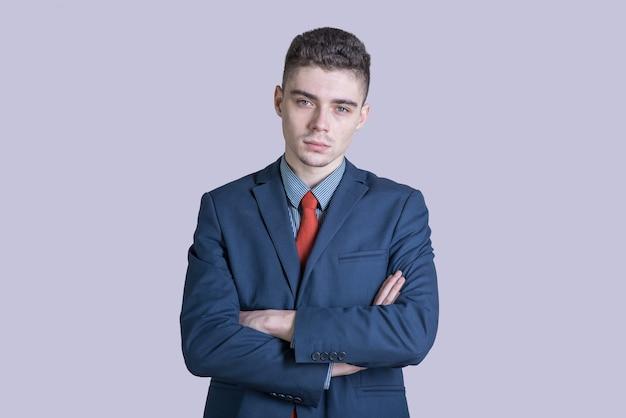 Portret młodego mężczyzny w garniturze z rękami skrzyżowanymi