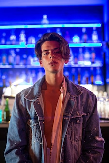Portret młodego mężczyzny w kurtce jean w nocnym klubie