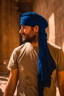 Portret młodego mężczyzny w niebieskim turbanie odwiedzającego świątynię edfu w pobliżu miasta asuan. egipt