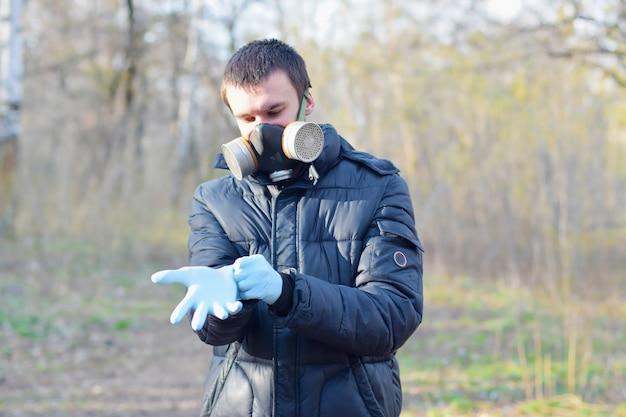 Portret młodego mężczyzny w ochronnej masce gazowej nosi gumowe rękawiczki jednorazowe