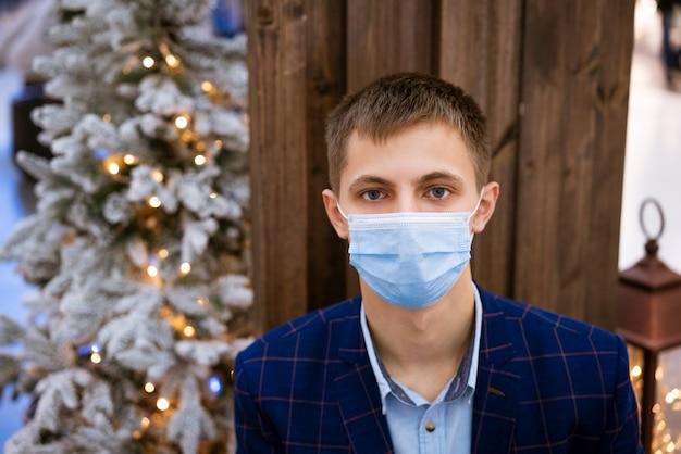 Portret młodego mężczyzny w ochronnej masce medycznej w niebieskiej kurtce na drewnianym tle