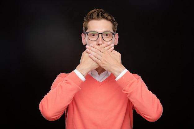 Portret młodego mężczyzny w okularach obejmujących usta rękami, nie czyniąc żadnego znaku mówiącego, na białym tle