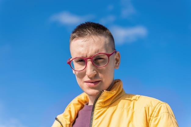 Portret młodego mężczyzny w okularach, patrzącego w kamerę, niebieskie niebo w tle