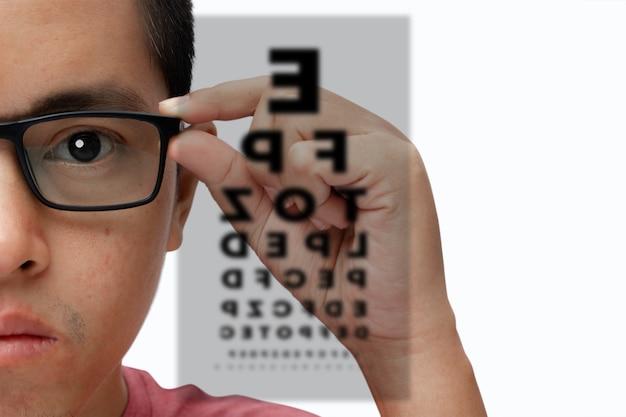 Portret młodego mężczyzny w okularach z wykresem badania wzroku na białym tle.