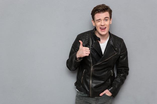 Portret młodego mężczyzny w skórzanej kurtce pokazujący kciuk do góry i mrugający na szarej ścianie