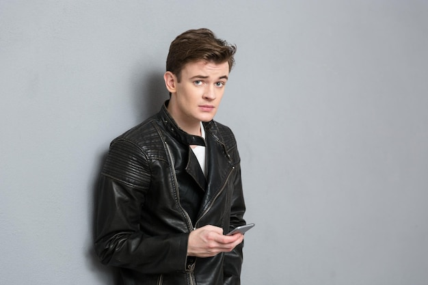 Portret młodego mężczyzny w skórzanej kurtce, trzymającego smartfona i patrzącego przez szarą ścianę
