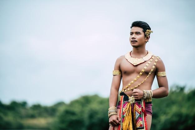 Portret młodego mężczyzny w tradycyjnym stroju pozuje w przyrodzie w tajlandii