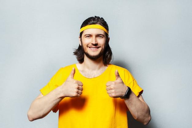 Portret młodego mężczyzny w żółtej koszuli pokazując kciuki do góry.