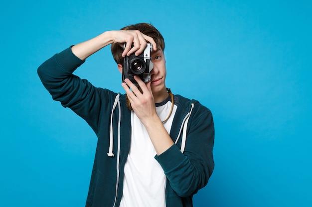 Portret młodego mężczyzny w zwykłych ubraniach, trzymającego robienia zdjęć na retro aparat fotograficzny na białym tle na niebieskiej ścianie. koncepcja życia szczere emocje ludzi.