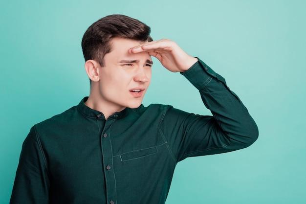 Portret młodego mężczyzny waha się odwracając głowę na turkusowym tle