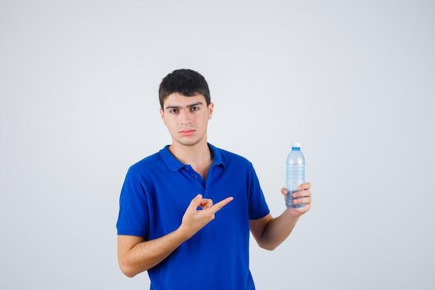 Portret młodego mężczyzny, wskazując na plastikową butelkę w t-shirt i patrząc pewnie z przodu