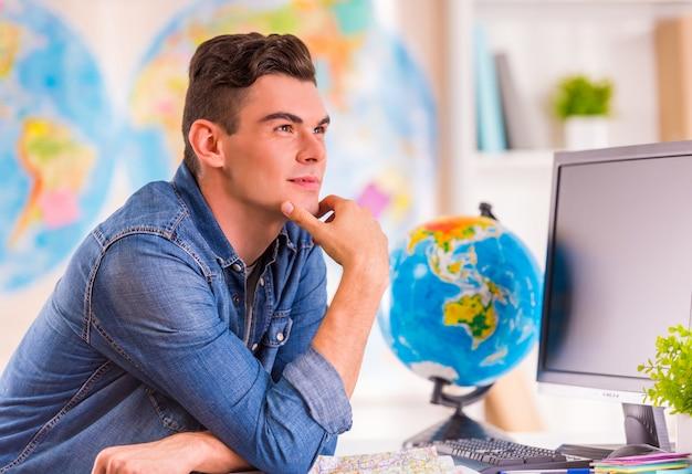 Portret młodego mężczyzny wybiera na podróż mapę.