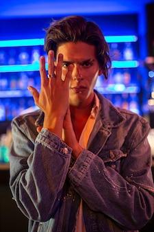 Portret młodego mężczyzny wyświetlono pierścionek zaręczynowy w nocnym klubie