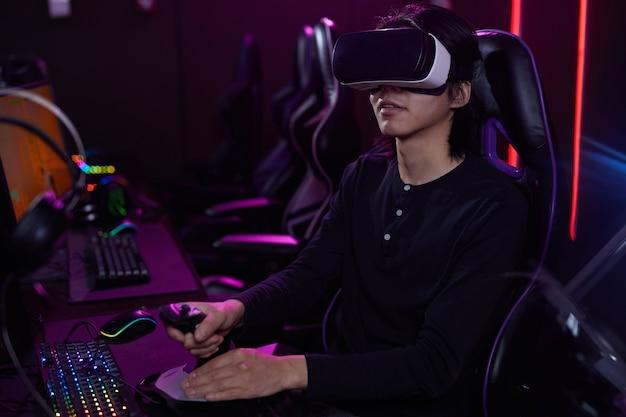 Portret młodego mężczyzny z azji noszenia zestawu vr podczas grania w gry wideo przy użyciu zmiany wyścigów w ciemnym wnętrzu cyber, kopia przestrzeń