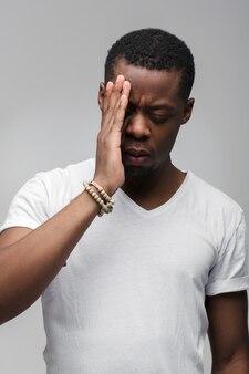 Portret młodego mężczyzny z bólem głowy na białym tle na szarej ścianie
