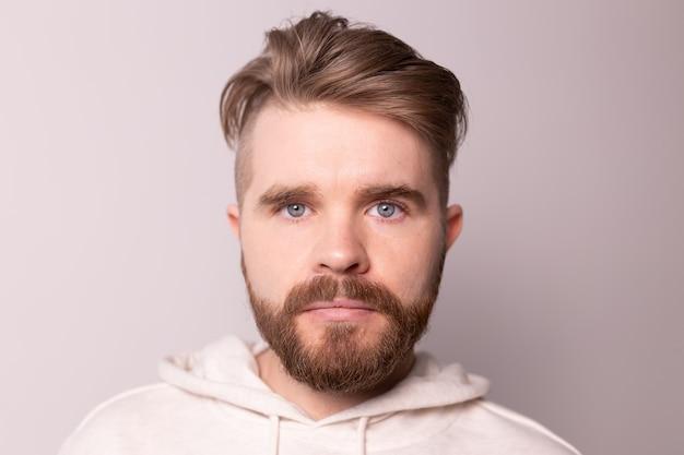 Portret młodego mężczyzny z brodą i wąsami oraz modną fryzurą nosi casualową bluzę z kapturem ma poważną sprawę